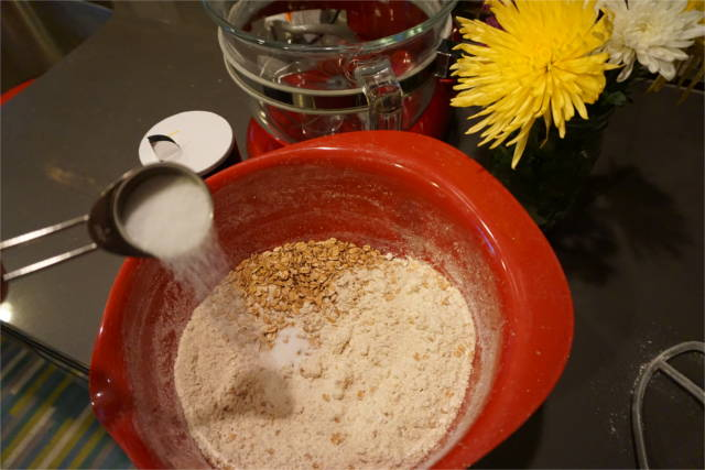 a tablespoon of sugar added to a mixing bowl with spelt flour and spelt flakes